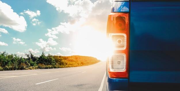 Auto blu parcheggiata sul ciglio della strada con la luce del sole e il cielo nuvoloso