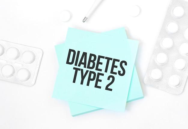 Carta blu con testo diabete tipo 2 su un tavolo con pillole e matita, concetto medico, vista dall'alto