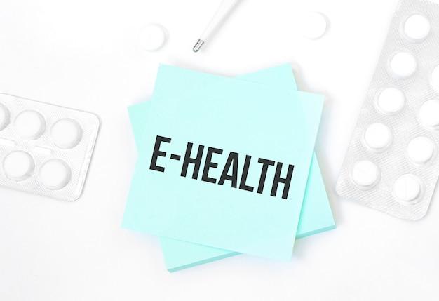 Carta blu con testo e-health su un tavolo con pillole e matita, concetto medico, vista dall'alto