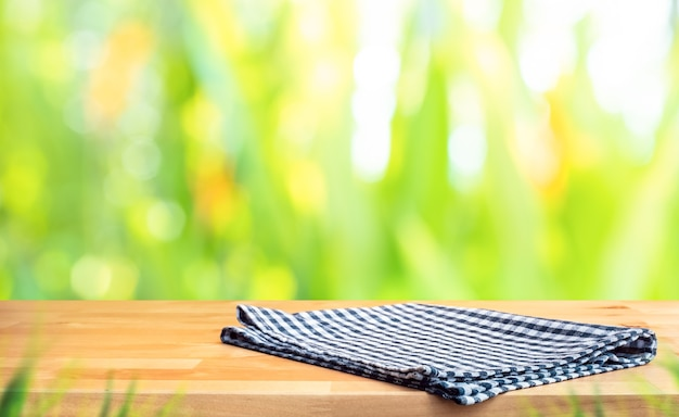 Tovaglia a quadretti blu su legno con sfondo sfocato cortile verde