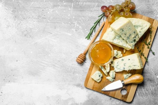 Formaggio blu con miele su una tavola di legno. su un rustico.
