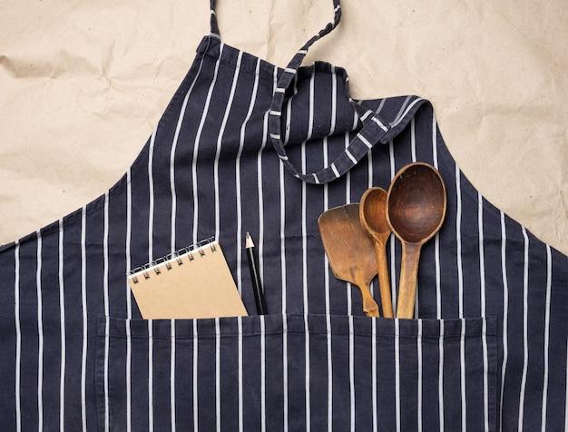 Grembiule da cuoco blu, all'interno di una tasca di cucchiai di legno, vista dall'alto