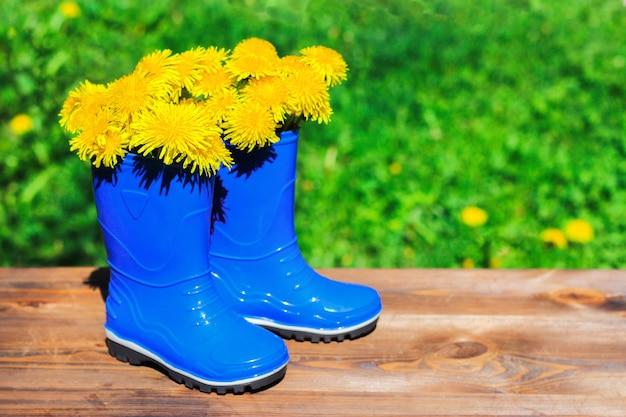 Stivali da pioggia blu per bambini con denti di leone gialli all'interno su tavola di legno e sfondo sfocato del giardino