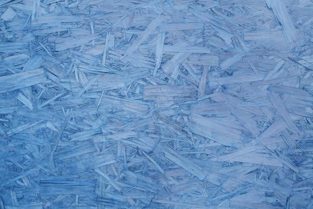 Compensato truciolare blu. primo piano di legno pressato. fondo: trucioli di legno. copia spazio