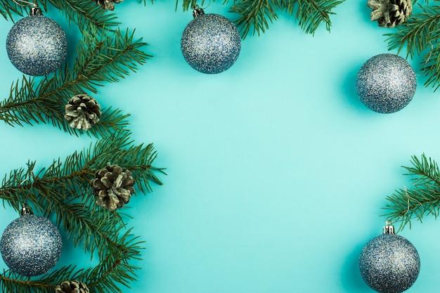 Sfondo di natale blu con rami di abete, coni e palline blu lucide. vista dall'alto. una copia dello spazio per il tuo testo.