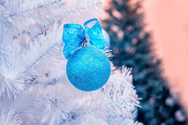 La palla blu di natale si blocca sull'albero di abete artificiale bianco