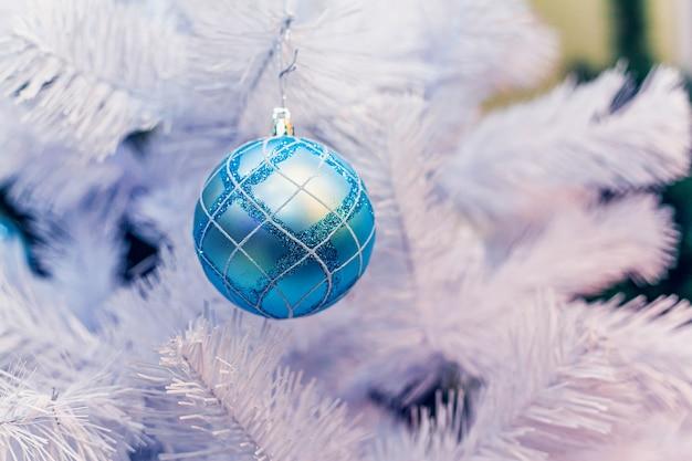 Le palle di natale blu si bloccano sull'albero di abete artificiale bianco