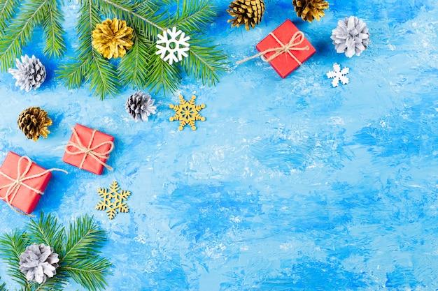 Cornice natalizia blu con rami di abete, scatole regalo rosse, decorazioni in argento e oro