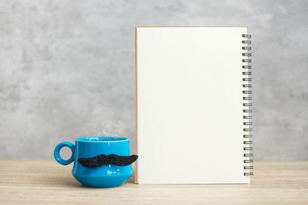 Tazza da caffè blu o tazza da tè con decorazioni di baffi neri e blocco note o calendario di carta vuoto sul tavolo. spazio in bianco della copia per testo. blue november, happy father day e international men day concept