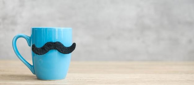 Tazza da caffè blu o tazza da tè con decorazioni di baffi neri sul tavolo. spazio in bianco della copia per testo. blue november, happy father day e international men day concept