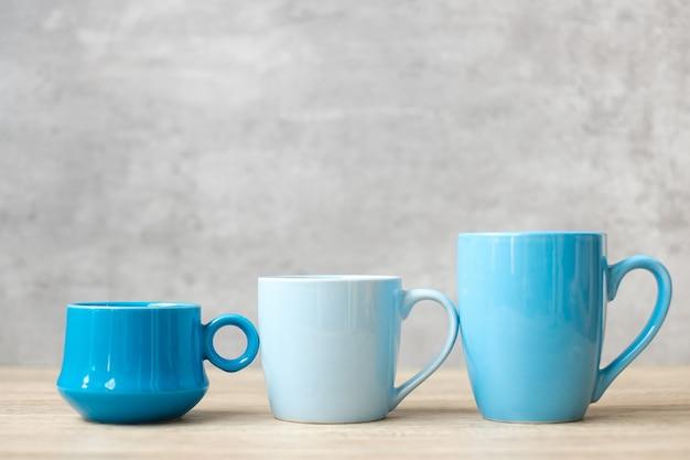 Tazza di caffè blu e tazza di tè sul fondo della tavola di legno al mattino, spazio vuoto per la copia per il testo. giornata internazionale del caffè e concetto di routine quotidiana
