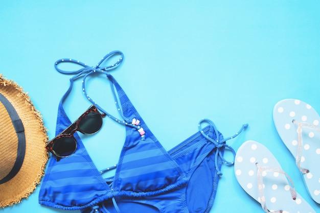 Bikini a colori azzurri, occhiali da sole, sandali a forma di cappello e polka su sfondo blu, collezione estate estiva piatta