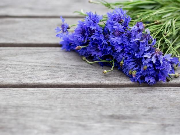 Fiori di fiordaliso blu, bouquet di fiori di campo estivo su fondo di legno grigio, spazio della copia
