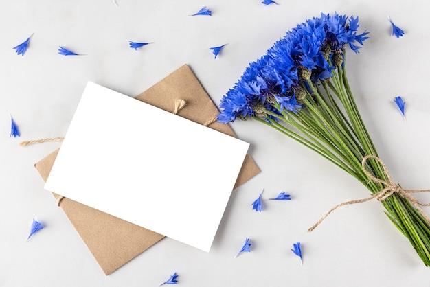 Mazzo di fiordalisi blu con biglietto di auguri vuoto e busta su superficie di marmo bianco