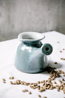 Caffettiera in ceramica blu artigianale cezve turco in piedi sulla tovaglia bianca con chicchi di caffè sopra. muro grigio dietro