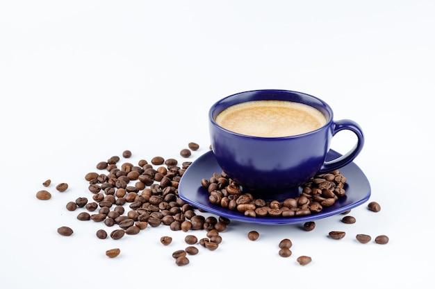 Tazza di caffè blu e chicchi di caffè su un piatto da portata su sfondo bianco