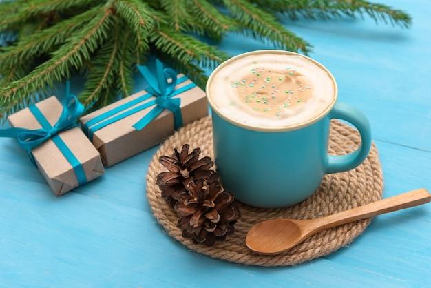 Una tazza di caffè blu su un tavolo di legno azzurro nella notte di natale.