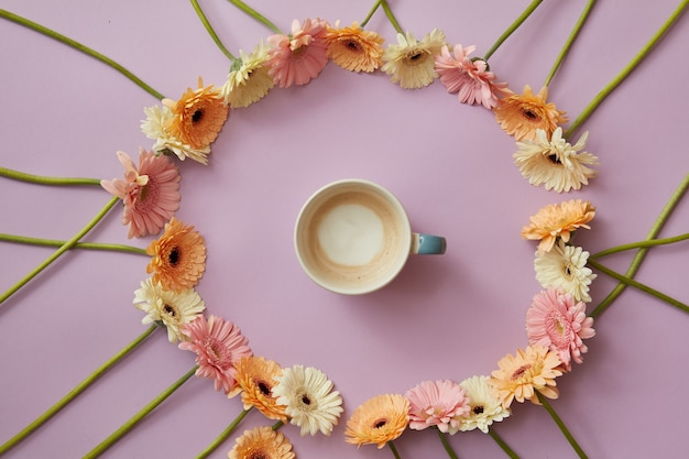 Tazza di caffè blu in una cornice rotonda di fiori colorati di gerbera su uno sfondo rosa con il concetto della festa della mamma