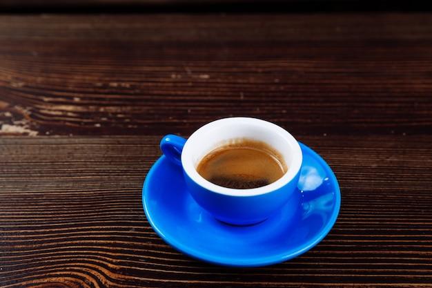 Tazza di caffè blu su uno sfondo di legno