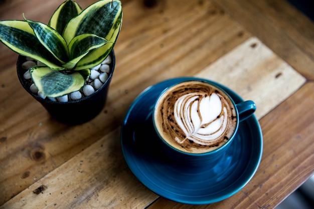 La tazza blu di cappuccino caldo è sulla tavola di legno