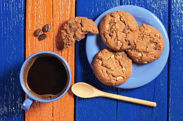 Tazza blu di caffè caldo con deliziosi biscotti al cioccolato su un tavolo di legno colorato, vista dall'alto