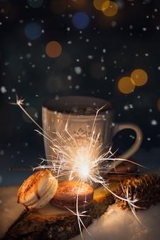 Una tazza blu con una bevanda calda e biscotti nella neve. concetto di vacanze invernali.