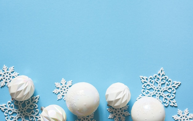 Sfondo di natale delicato blu con palline bianche. luci bokeh. arredamento di capodanno. i regali.