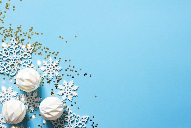 Sfondo di natale delicato blu con palline bianche. luci bokeh. arredamento di capodanno.