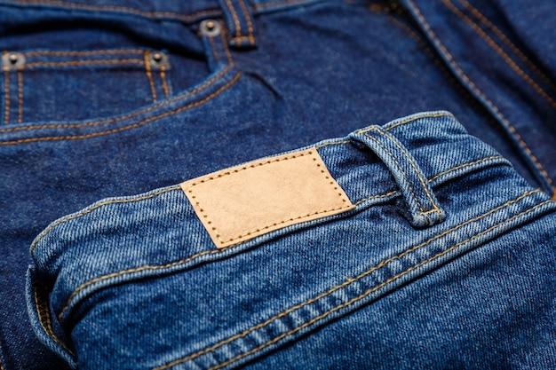 Jeans in denim blu con etichetta vuota. etichetta marrone in pelle vuota su sfondo di pantaloni in denim. etichetta in pelle beige mockup vuoto. avvicinamento.