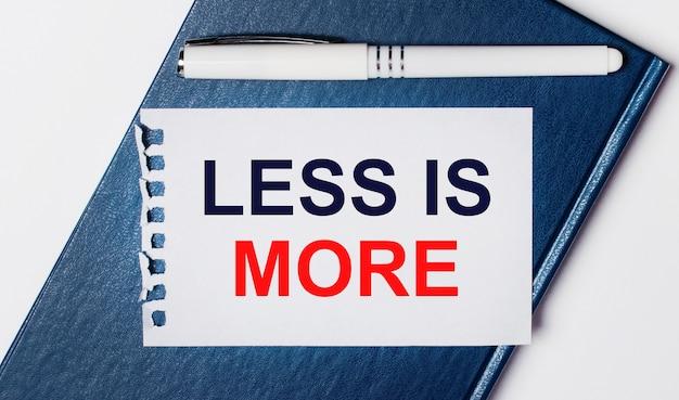 Il diario blu giace su uno sfondo chiaro. su ha una penna bianca e un pezzo di carta con il testo less is more.