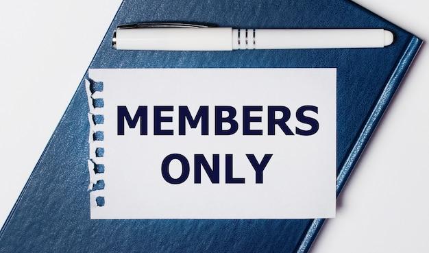 Il diario blu giace su uno sfondo chiaro. su ha una penna bianca e un pezzo di carta con il testo solo membri.