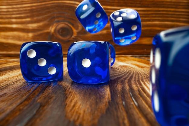 Cubi di dadi blu contro la fine di legno marrone su