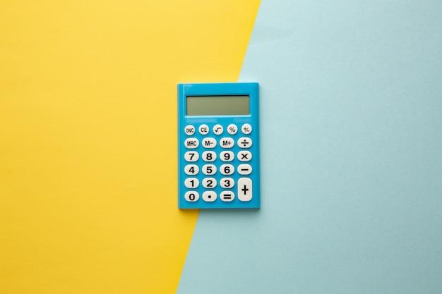 Calcolatrice digitale blu su sfondo giallo-blu. spazio per la tua iscrizione.