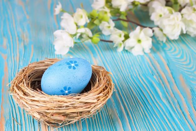 Uovo di pasqua blu nel nido e ramo di paglia con i fiori su fondo di legno blu con spazio per testo.