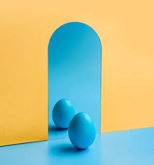 Un uovo blu davanti a uno specchio su uno sfondo di giallo e blu. moderno concetto di pasqua.