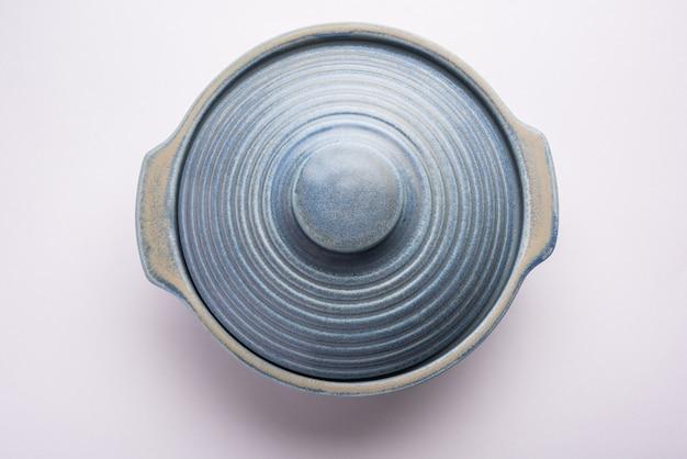 Ciotola o contenitore in ceramica vuota blu con coperchio, isolata su una superficie piana