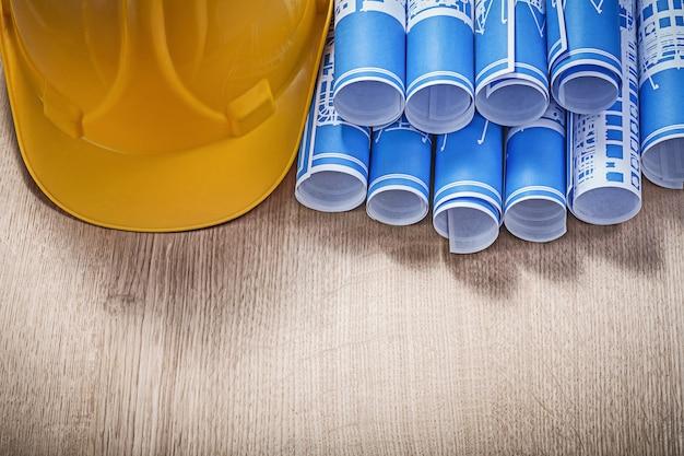 Disegni tecnici blu che costruiscono casco su tavola di legno