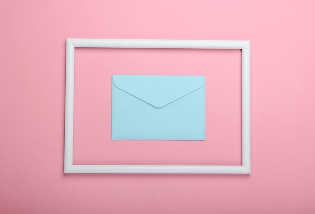 Busta blu in una cornice bianca su superficie rosa