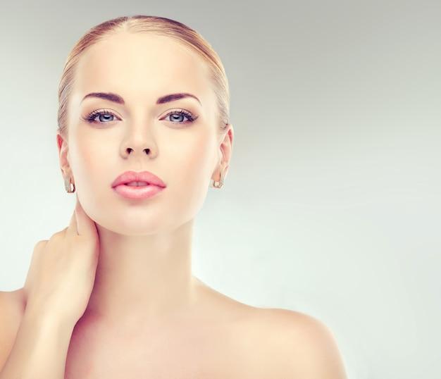 La giovane donna dagli occhi azzurri e attraente con un trucco espressivo e un rossetto rosa sulle labbra guarda dritto nello spettatore. cosmetologia di trucco di bellezza.
