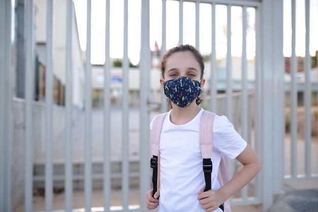 Ragazza caucasica dagli occhi azzurri in attesa di entrare a scuola nella nuova normalità con una maschera