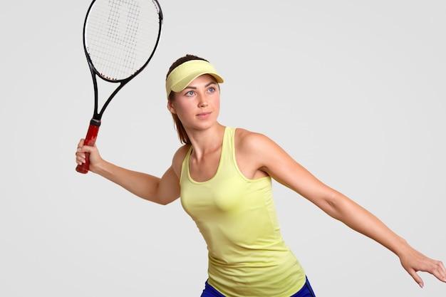 La bella donna dagli occhi blu vestita di abiti sportivi, pronta a colpire la palla, ha concentrato lo sguardo in lontananza, gli piace giocare a tennis, isolato su bianco, si trova in una posizione pronta. concetto di sport