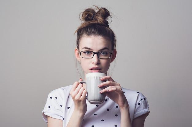 Giovane donna dagli occhi blu in occhiali, indossa una camicia bianca a pois, tenendo in mano un caffè