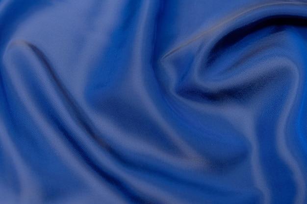 Fondo blu di struttura del tessuto, colore blu morbido del tessuto ondulato, struttura del panno di seta o del raso di lusso.
