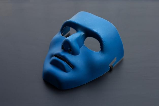 Maschera facciale blu su sfondo scuro.