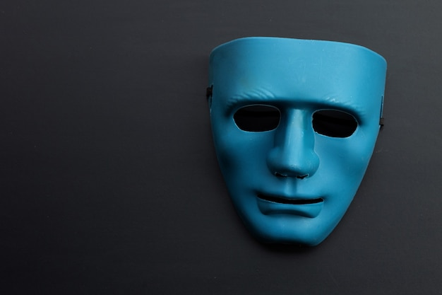 Maschera viso blu su superficie scura. copia spazio