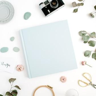 Album di foto di famiglia o matrimonio blu, foglia di eucalipto, fotocamera retrò e boccioli di rosa secchi su bianco