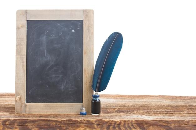 Penna piuma blu sulla tavola di legno con lavagna vuota
