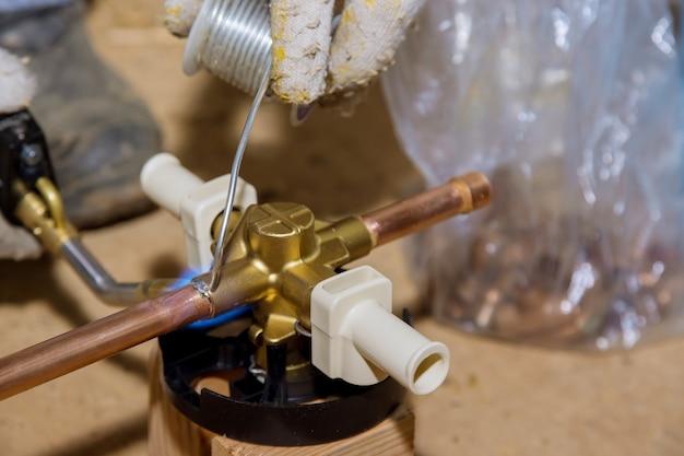 Cannello a fiamma blu che salda un deviatore in ottone per vasca da bagno con doccia