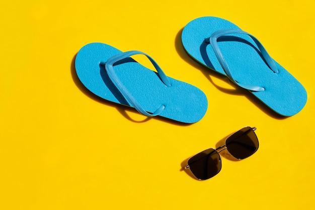 Infradito blu con occhiali da sole su sfondo giallo. goditi il concetto di vacanza estiva.