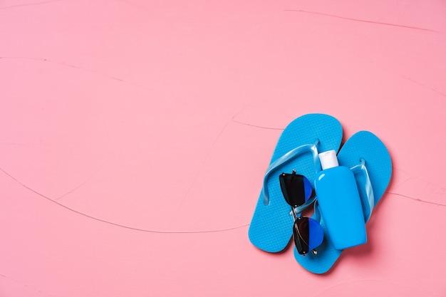 Infradito blu con crema solare e occhiali da sole su rosa, piatto lay